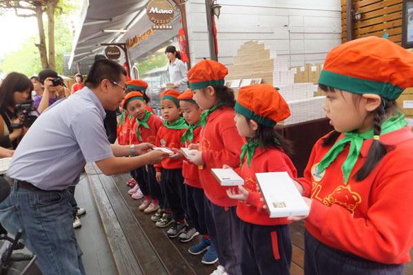 埔里教育-小朋友從茆晉詳董事長手中拿到巧克力都露出開心的笑容。(唐茹蘋攝)